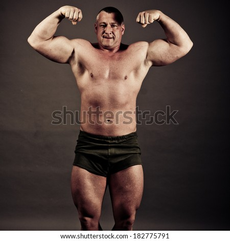 Bodybuilder posing over gray background -colorized photo for dramatic mood