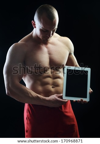 Bodybuilder posing with tablet for copy space - stock photo