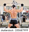 Bodybuilder shakes his back on the simulator. Back view - stock photo