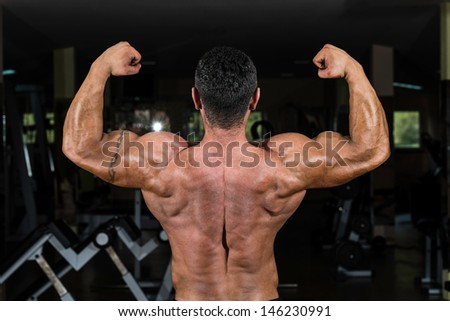bodybuilder showing his back double biceps - stock photo