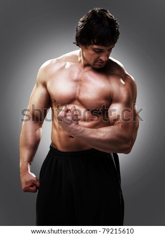 Bodybuilder showing his left biceps - stock photo