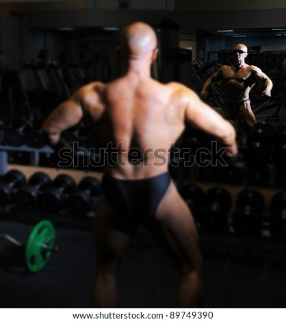 bodybuilder showing his muscles in the gym focus on the reflection in the mirror - stock photo