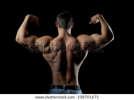 Bodybuilder showing his muscles. on a black background - stock photo