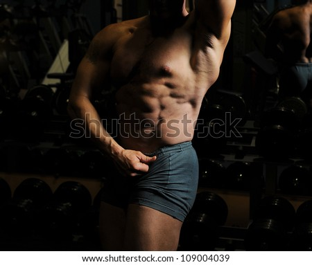 Bodybuilder showing his muscles on a black background - stock photo