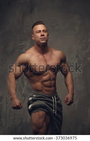 Bodybuilder showing his muscular torso. - stock photo