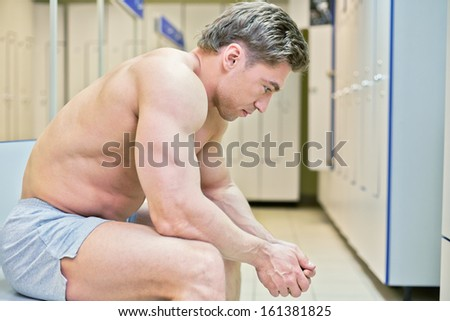 Bodybuilder sits tired in locker room after finishing training - stock photo