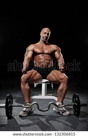 Bodybuilder sitting on workout bench in gym with barbell isolated on black - stock photo