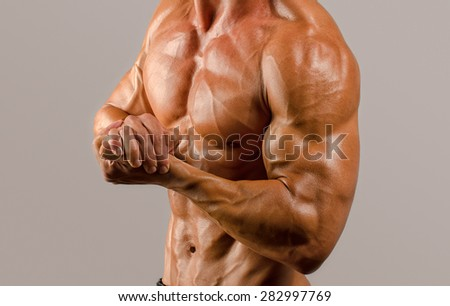 Bodybuilder topless, flexing his muscles. Strong man with perfect abs, shoulders,biceps, triceps and chest - stock photo