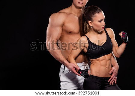 Bodybuilder touches girl flexing bicep. Girl flexing arm near guy. Learning how to pose. Future fitness model. - stock photo