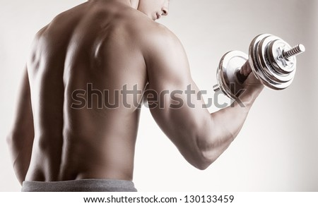 Bodybuilder training with dumbbells on black background. Rear view - stock photo