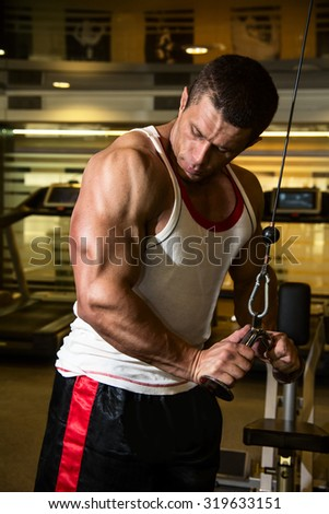 Bodybuilder trains the muscles in the gym. fitness training - stock photo