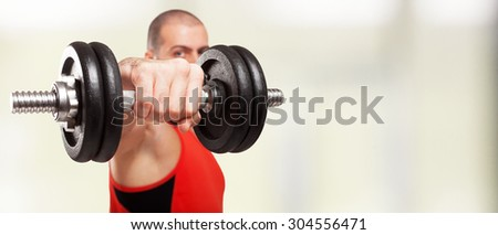 Bodybuilder using a dumbbell to work out. Large copy-space