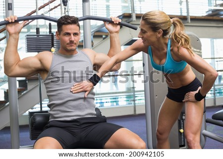 Bodybuilder using weight machine for arms with encouraging trainer at the gym - stock photo