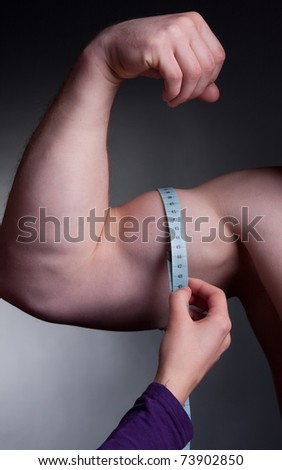 bodybuilder with a measuring tape around his bicep - stock photo