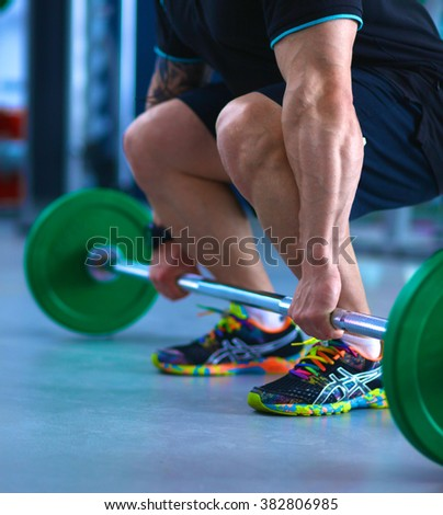 Bodybuilder with barbell in gym - stock photo