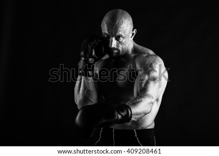 Bodybuilder with boxing gloves on a black background - stock photo