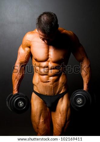 bodybuilder with dumbbells on black background - stock photo