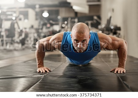 bodybuilder working out and doing push upsat the gym while  - stock photo