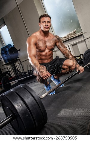 Bodybuilders workout with bar in a gym - stock photo