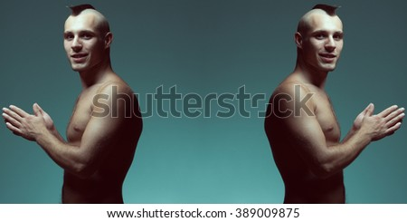 Bodybuilding and body sculpture concept. Beautiful (handsome) bald with mohawk muscular male model with perfect body posing over blue background. Sport street style. Copy-space. Fashion studio shot - stock photo