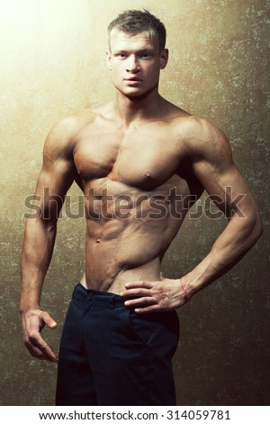 Bodybuilding and body sculpture concept. Beautiful (handsome) muscular male model with perfect body posing over golden background. Studio shot - stock photo