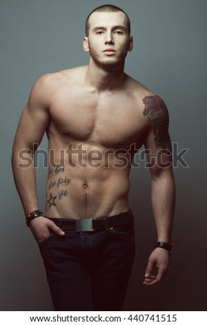 Bodybuilding and body sculpture concept. Beautiful (handsome) muscular male model with perfect body posing in blue jeans over gray background. Hand in pocket. Street style. Studio shot