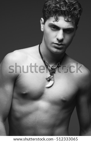 Bodybuilding and body sculpture concept. Beautiful (handsome) muscular male model with perfect body posing over golden background. Ethnic necklace with tooth. Close up. Monochrome studio shot