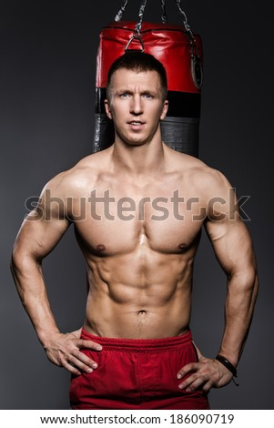 Bodybuilding. Attractive man with boxing bag - stock photo