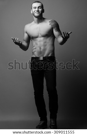 Bodybuilding, body sculpture concept. Male model with perfect body posing over gray background. Hands in pockets. Deep shadows. Full length portrait. Street style. Black white, monochrome studio shot - stock photo