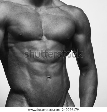Bodybuilding concept. Beautiful (handsome) muscular male model with perfect body posing over light-gray background. Close up. Monochrome studio shot - stock photo