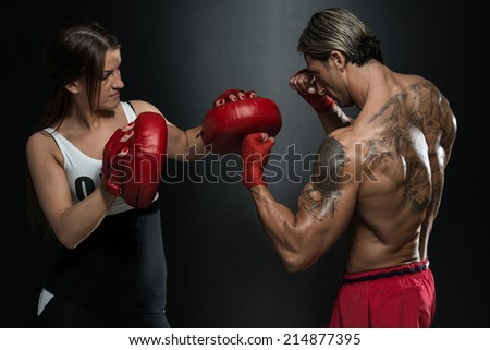 Bodybuilding Couple Posing With Boxing Gloves On Black Background