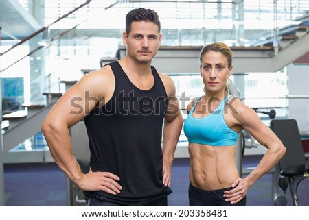 Bodybuilding man and woman frowning at camera at the gym - stock photo