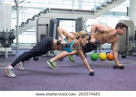 Bodybuilding man and woman holding dumbbells in plank position at the gym - stock photo