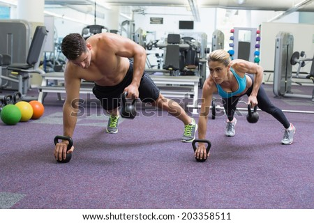 Bodybuilding man and woman lifting kettlebells in plank position at the gym - stock photo