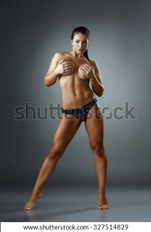 Bodybuilding. Shot of tanned woman posing topless - stock photo