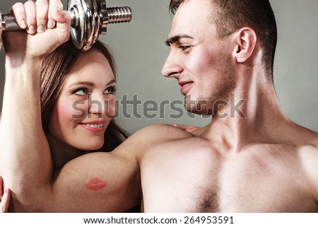 Bodybuilding. Strong fit man exercising with dumbbells. Closeup muscular guy flexing lifting weights, lovely girl looking admiringly kissing his biceps. - stock photo