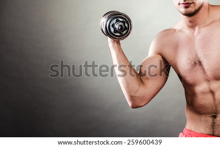 Bodybuilding. Strong fit man exercising with dumbbells. Closeup muscular young guy lifting weights dark background - stock photo