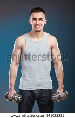 Bodybuilding. Strong fit man exercising with dumbbells. muscular young guy lifting weights dark blue background - stock photo