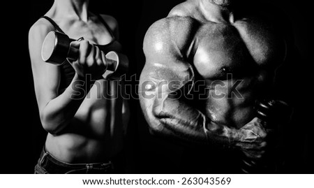 Bodybuilding. Strong man and a woman posing on a black background - stock photo
