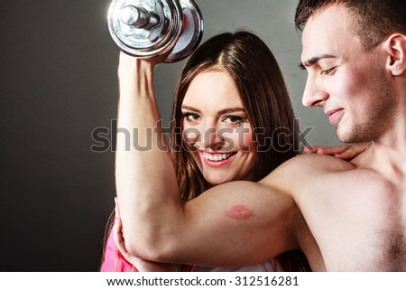 Bodybuilding. Strong man exercising with dumbbells. Closeup muscular guy flexing lifting weights, girl looking admiringly kissing his biceps. - stock photo