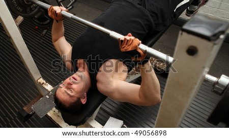 bodybuilding workout in gym. Male lifting barbell. man under exercise equipment training upper body strength - stock photo