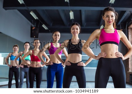 Bodycare, Sport, health, weight loss,  beauty, wellness and wellbeing concept. Six Multiracial beautiful young sport ladies are standing in line in the gym and smiling
