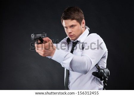 Bodyguard. Confident young man in shirt and tie holding gun and aiming somewhere while standing against black background - stock photo