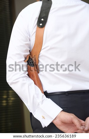 Bodyguard in a white shirt with a tie and a pistol vertical photo - stock photo