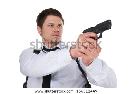 Bodyguard. Low angle view of confident young man aiming with gun while standing isolated on white - stock photo