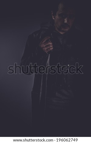 Bodyguard, portrait of stylish man with long leather jacket, gun armed - stock photo