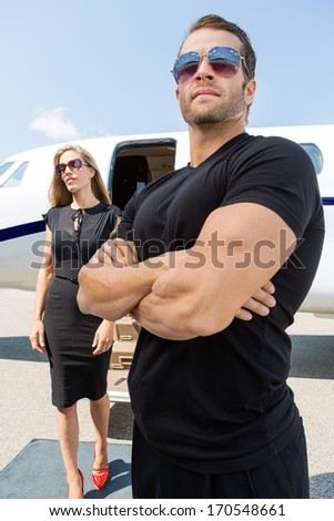 Bodyguard with arms crossed standing against woman and private jet - stock photo