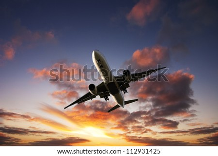 Boeing 777 jet aeroplane landing from bright dramatic sunset moody sky. - stock photo