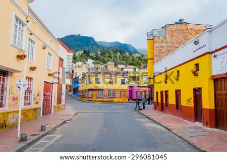 BOGOTA, COLOMBIA - FEBRUARY 25, 2015: Charming neighbourhood of colorful two storey townhouses with a stone paved street going up and green hills in background - stock photo