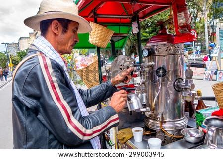 BOGOTA, COLOMBIA - FEBRUARY 25, 2015: Unidentified street vendor selling fresh coffee at Candelaria neighborhood in Bogota Colombia - stock photo